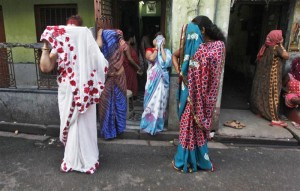Indian sex workers cover their faces as they react to the camera while watching a rally as part of the week-long sex workers' freedom festival at the Sonagachi red-light area in Kolkata July 24, 2012. In the global battle against HIV/AIDS, sex workers like those in Sonagachi, one of Asia's largest red light districts, are a crucial link in a chain of infection that some 20,000 experts gathered in Washington are debating how to break -- but without having foreign sex workers there. Picture taken on July 24, 2012. To match story INDIA-SEXWORKERS/  REUTERS/Rupak De Chowdhuri (INDIA - Tags: HEALTH SOCIETY)