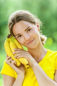 young woman in yellow blouse with banana
